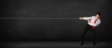 Dragande rep för affärsman på grå bakgrund Fotografering för Bildbyråer