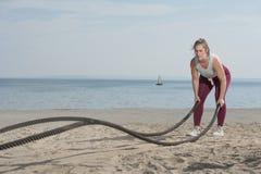 Dragande rep för idrotts- kvinna på sjösidan arkivfoto