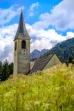 Dragar tornet för den kyrkliga klockan för landet bland gräset Arkivbild