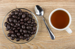 Dragee peanuts in cacao powder, tea and teaspoon on table Stock Image