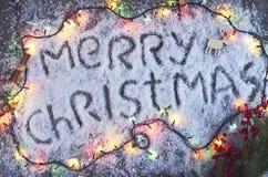 Dragen bokstäver för glad jul hand med ljus över det wood brädet Arkivfoto