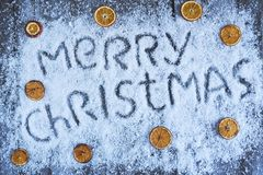 Dragen bokstäver för glad jul hand med orange frukt över trä Royaltyfria Bilder