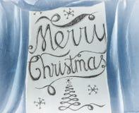 Dragen bokstäverdesign för glad jul som hand inramas av blå curta Royaltyfri Fotografi