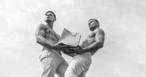 Dragen de kerels die aantrekkelijke tweelingen het winkelen zak uit pakpapier wordt gemaakt De greep van mensen de spieratleten h stock fotografie