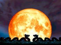 dragen superbe de double de lune de plein sang sur le ciel nocturne de toit Photo libre de droits