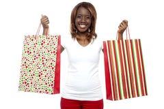 Dragende het winkelen van de vrouw zakken in de beide handen Royalty-vrije Stock Foto's