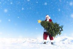 Dragende Kerstmisboom van de Kerstman op sneeuw behandelde berg Royalty-vrije Stock Afbeeldingen