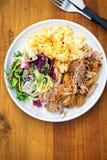 Draget griskött med mosade potatisar och blandad sidasallad på den vita plattan Arkivbild