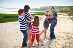 Dragkamp - familj som spelar på stranden Royaltyfria Bilder