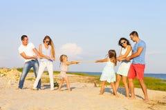 Dragkamp - vänner som spelar på stranden Arkivfoton