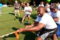 Dragkampen Teams handtagrepet i Fundraising händelse för sommar Arkivbilder