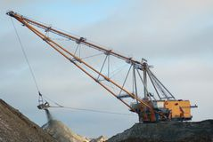 Dragline in open pit. Heavy dragline in open cast mining quarry in winter time Royalty Free Stock Image