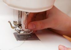 Dragning av en tråd i en symaskin Royaltyfri Bild