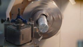 Dragning av metalldelar på drejbänkmaskinen på fabriken, massor av metallshavings, industriellt begrepp, främre sikt Arkivfoto