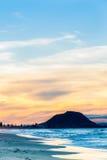 Dragning för blått för ensembler för inställningssol på vatten och strand och orange moln Royaltyfria Bilder