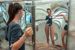 Dragning flicka som ser hennes bild i den förvridna spegeln i korridoren av speglar arkivbild