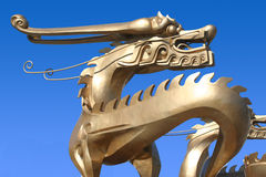 Dragon. Gold dragon with blue sky background Royalty Free Stock Image
