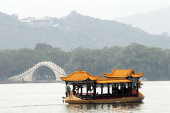 Dragon boat. A dragon boat next to an ancient bridge in a scenery park Stock Photography