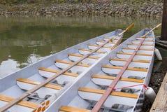 Dragon boats docked at a marina. Long dragon boats docked in a marina with a rock wall and water Stock Photos