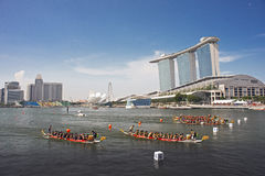 Dragon boats streaming into finish with MBS as backdrop Stock Images