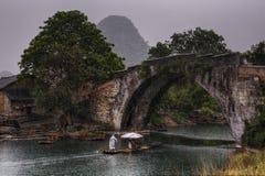 Dragon Bridge in Yulong Village, Yangshuo, Guilin, Guangxi Provi. Yangshuo, Guangxi, China - March 31, 2010: Dragon Bridge in Yulong Village, tourists make a Royalty Free Stock Photography