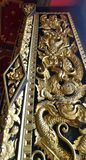 Dragon carving on  temple windor cover with Thai Art design   with Lacquer coated Real Gold Leaf in royal temple Bangkok Thailand Stock Photos