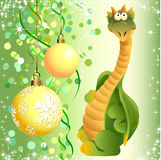 The Dragon and the christmas decorations. Funny green dragon toy on the background of Christmas decorations Royalty Free Stock Photo