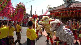 Dragon dance and lion dance perform under hot sunny day at Chew Jetty.