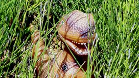 Dragon dinosaur in the thickets of green horsetail. Toy. Production. stock photo