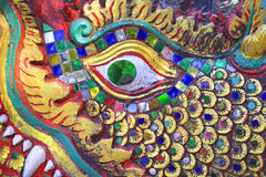 Dragon Eye. Green glittering eye of a dragon/serpent set in a multi-colored bejelled sculpture at Doi Suthep Temple in Chiang Mai, Thailand Royalty Free Stock Image