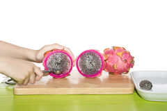 Dragon fruit is being made into balls on a white plate. Stock Images