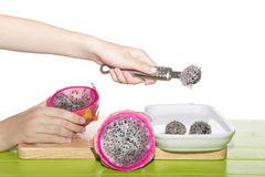 Dragon fruit is being made into balls on a white plate. Stock Photos
