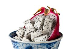 Dragon fruit cut in half in a blue bowl against a white background. Dragon fruit cut in half with distinctive red skin in a blue pottery bowl isolated against a Royalty Free Stock Photos