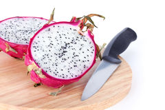 Dragon fruit and knife on wooden cutting board Royalty Free Stock Images