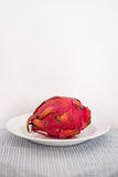 Dragon fruit on a plate. Beautiful and exotic dragon fruit or pitaya lays on a white plate Royalty Free Stock Photo