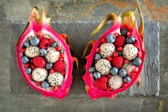 Dragon fruit salads with berries over slate stock photo