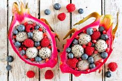 Dragon fruit salads with berries over white wood. Colorful dragon fruit salads with raspberries and blueberries over a white wood background Stock Images