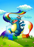 A dragon at the hilltop and a rainbow in the sky Royalty Free Stock Image