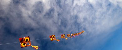 Dragon Kites To Infinity. A long string of dragon kites reaches far into a wide blue sky Royalty Free Stock Images