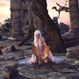 Dragon Lady. A beautiful woman playing with a little dragon. A fantasy scene with dragons, castle and ruins Royalty Free Stock Photo