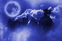 Dragon in moonlight. Dragon silhouette over rocks in a blue sky royalty free stock images