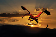 The dragon and the samurai. A red dragon and a samurai fight, at the foreground of a sunset Royalty Free Stock Image