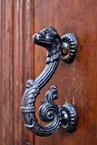 Dragon-shaped handles of an ancient door. Antique door with handles to open in the shape of a burnished and aged metal dragon stock photography