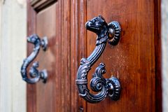 Dragon-shaped handles of an ancient door. Antique door with handles to open in the shape of a burnished and aged metal dragon royalty free stock photography