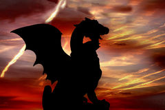 Dragon silhouette. Against red evening sky Stock Photos
