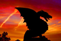 Dragon silhouette. Against red evening sky Stock Photo