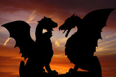 Dragon silhouettes. Against red evening sky Royalty Free Stock Images