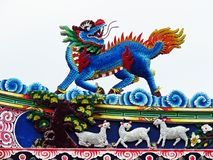 Dragon statue flying Chinese temple roof in Thailand stock photo