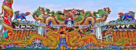 Dragon statue flying Chinese temple roof in Thailand stock images