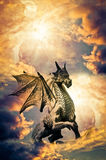 Dragon. A statue of dragon with shadow behind him over sunset sky with copy space stock photography